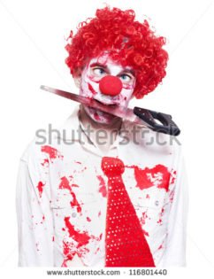 stock photo isolated creepy clown wearing bright red wig holding bloody saw in mouth in a depiction of a horror 116801440